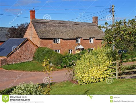 thatched cottage next to a rural royalty free