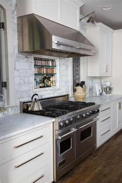 Stainless kitchen hood over large stove connected by white tile backsplash and wood kitchen