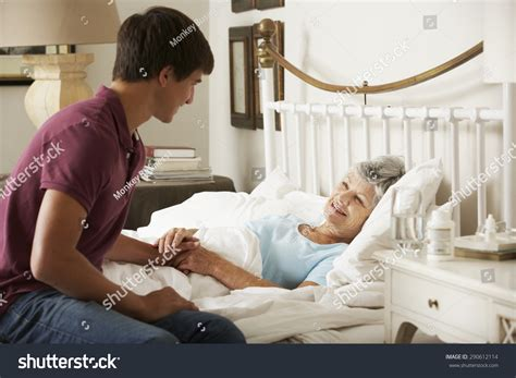 futon pflege grandson visiting grandmother in bed at home stock