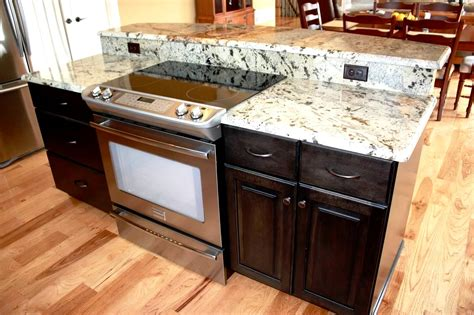 kitchen island with stove and seating island with storage slide in range and breakfast bar
