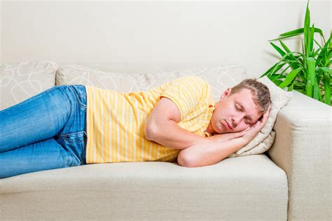 lay down on the sofa tired man lay down to take a nap on the sofa stock photo