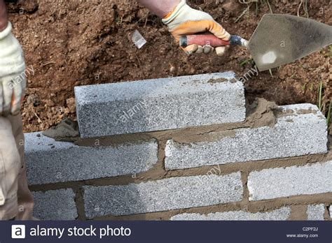 building a wall bricklayer with trowel building a wall with half cement blocks stock photo royalty free
