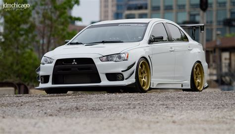 white mitsubishi lancer with black rims white paint gold rims and black yes this is