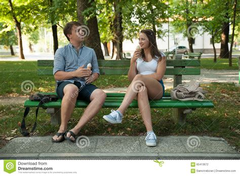 eating bench young couple eating ice cream in shadow on a bench in park on ho stock photo image