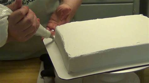 icing a quarter sheet cake with an easy icer and adding