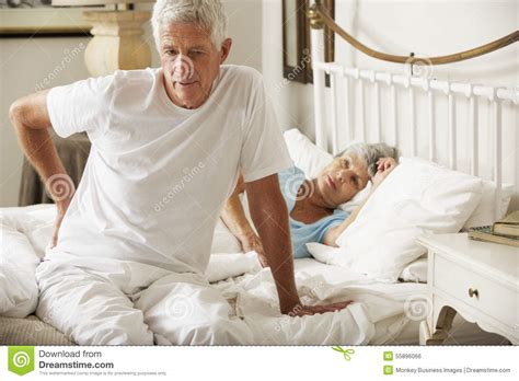 out of bed senior man suffering from backache getting out of bed