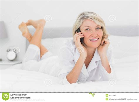 how to make a woman happy in bed happy woman making a phone call lying on bed stock photo