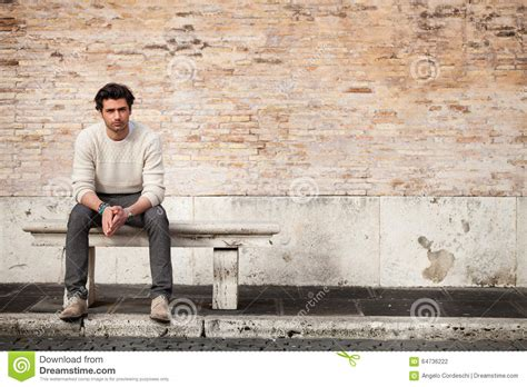 man sitting on bench handsome young man sitting on marble bench with bricks