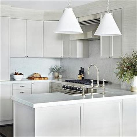 Peninsula Kitchen Sink white and gray kitchen with marble backsplash