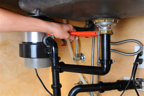 Plumber Using Wrench Under Kitchen Sink Royalty Free Stock