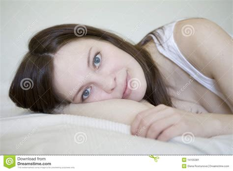 lying on bed young woman in white lying on bed stock image image