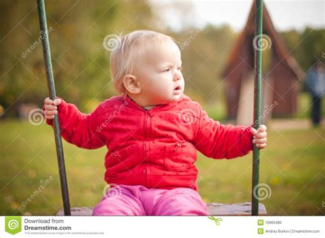 girl swinging young cute girl swinging on playground in park stock photo