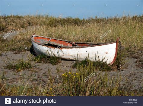 row boat en francais abandoned old double ended rusting metal row boat beached