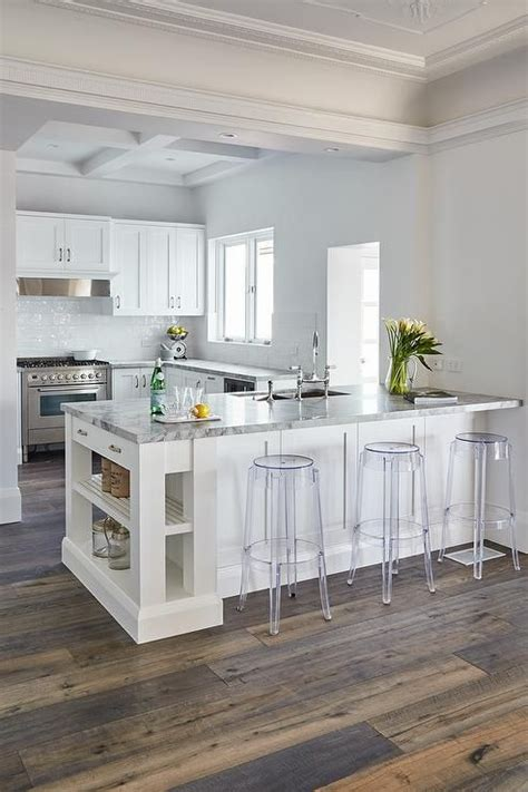 peninsula island kitchen backless acrylic stools sit in front of a white kitchen peninsula accented with slated shelves