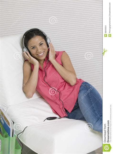 woman reclining woman reclining on chair listening to music on headphones