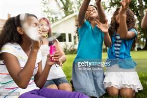 backyard babes girls blowing bubbles in backyard stock photo getty images