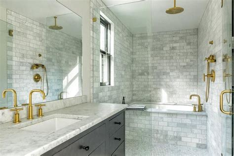 gold and gray bathroom features a large seamless glass