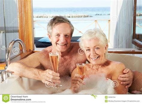couple bathtub senior couple relaxing in bath drinking chagne together