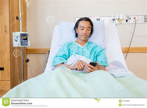man using cell phone in bed stock images image 33817024 patient text messaging through cell phone on royalty free