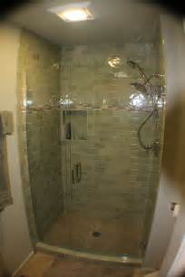 Tiled shower frameless glass door and hand shower compliment this