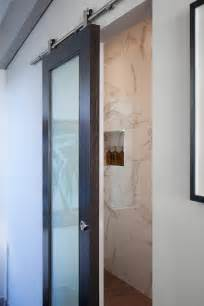 Wood and glass barn door to bathroom enter this bathroom in ultimate