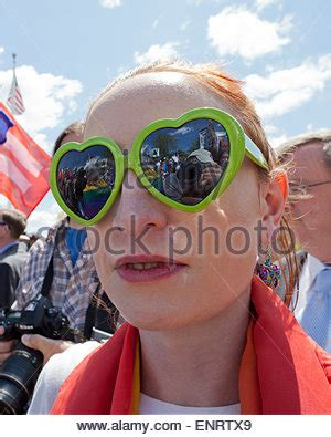 woman wearing heart shaped sunglasses, blowing a kiss at