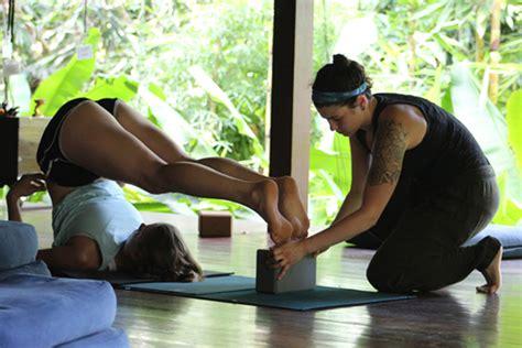 yoga teacher assisting student peak beings yoga