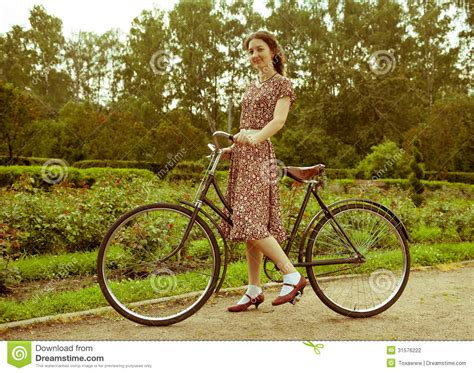 retro photos young woman in dress posing with retro bicycle in the park