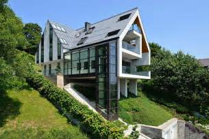 House on a slope connects to its surroundings through a glass