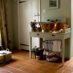 Terracotta tiles in kitchen with console table floor length curtains