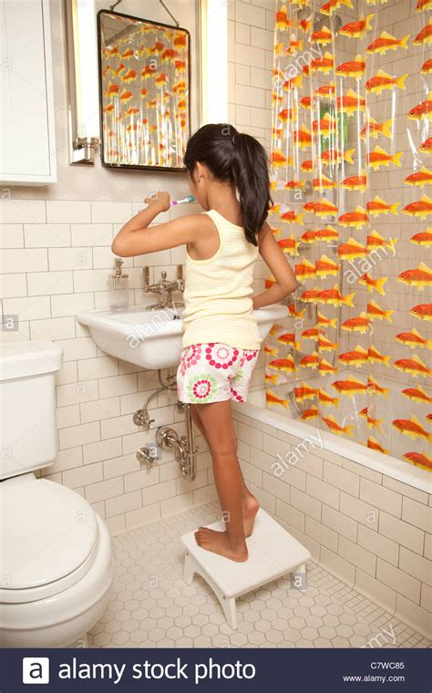 girl in the bathroom young girl in bathroom brushing teeth stock photo royalty