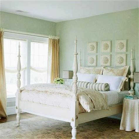 bedroom with green walls sand colored curtains and bedding and rug with sea foam