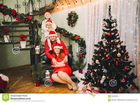 happy family sitting near christmas tree in red stock