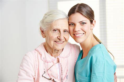 smiling caregiver embracing happy senior in nursing