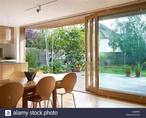 Large Glass Doors Residential Wooden Dining Table And Chairs In Front Of Large Sliding Glass Doors Stock Photo Royalty Free