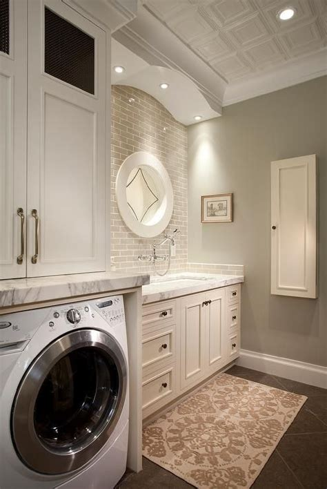 white and gray laundry room features white cabinets paired