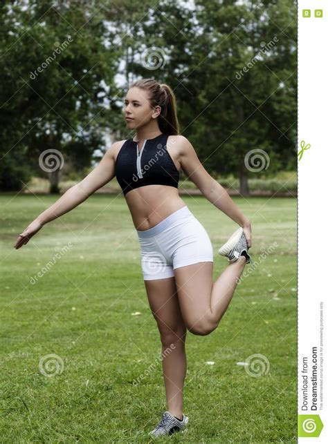 young girl up shorts teen caucasian woman stretching outdoors in park stock