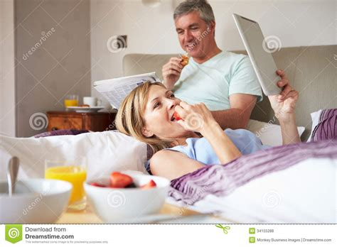 eating in bed couple eating breakfast in bed with paper and digital