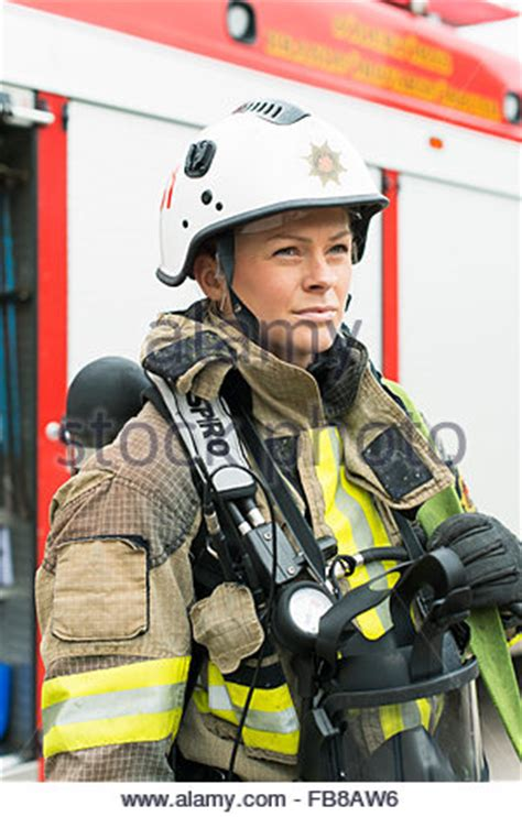 portrait of a firefighter with fire in background stock