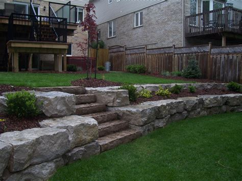 retaining wall to level backyard backyard multi level stone wall and flowerbeds feature natural stone features