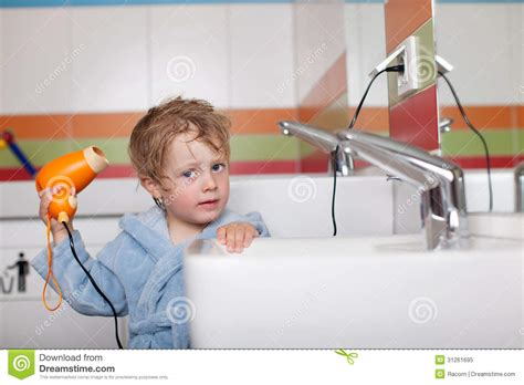 Hair Dryer In A Bathtub boy using hair dryer in bathroom royalty free stock photo