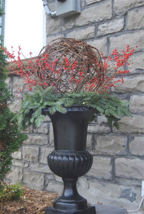 christmas decorating huge stone urns in front of entrance winter and topiaries on