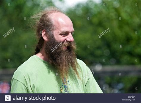 ponytails for bald men a man with a bald head but a very long beard and a pony