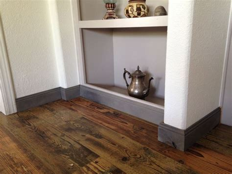 Barnwood laminate flooring and grey baseboards in my house