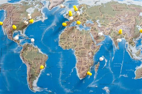 image of world map image of thumb tacks in various locations on world map