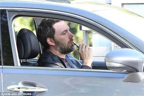 ben affleck puffs on an e cigarette as he gets a parking