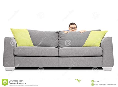 behind couch frightened man hiding behind a sofa stock image image