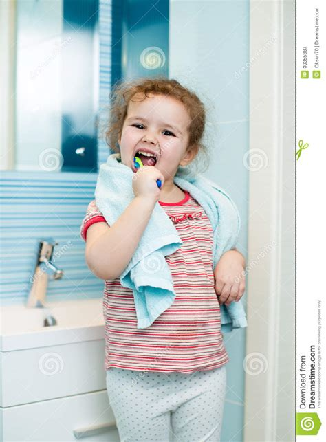 kid in bathroom kid girl brushing teeth in bathroom royalty free stock
