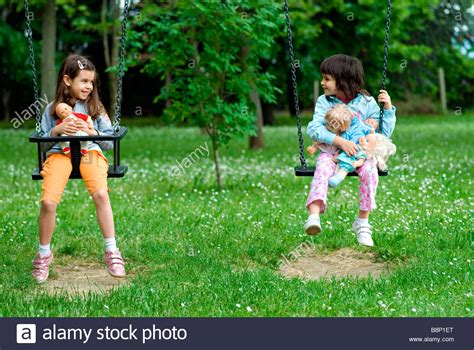 the swing girls little girls on the swing stock photo royalty free image