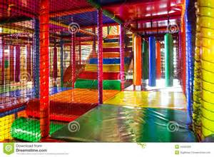 kids running inside a colorful indoor playground stock